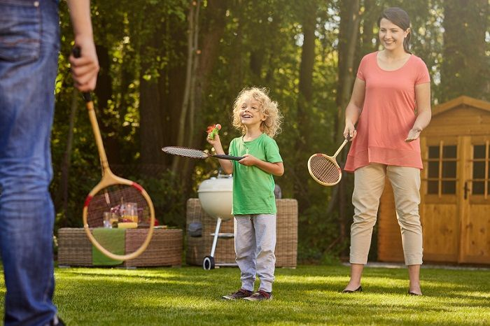 Boy playing badminton with parents