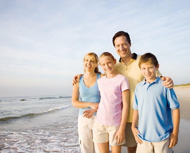 Smiling family on beach.